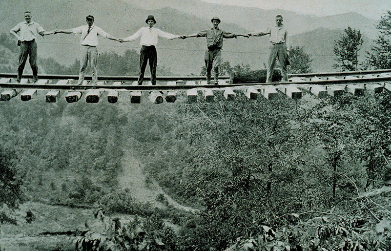 Landslides left this railroad track suspended in mid-air, but these daring men still stood on the rails for a photo.Photograph by Steve Nicklas, NOS, NGS; courtesy of National Oceanic and Atmospheric Administration/Department of Commerce.