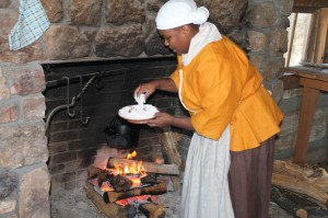 Clifton places chicken to cook in a cast iron pot over an open hearth.