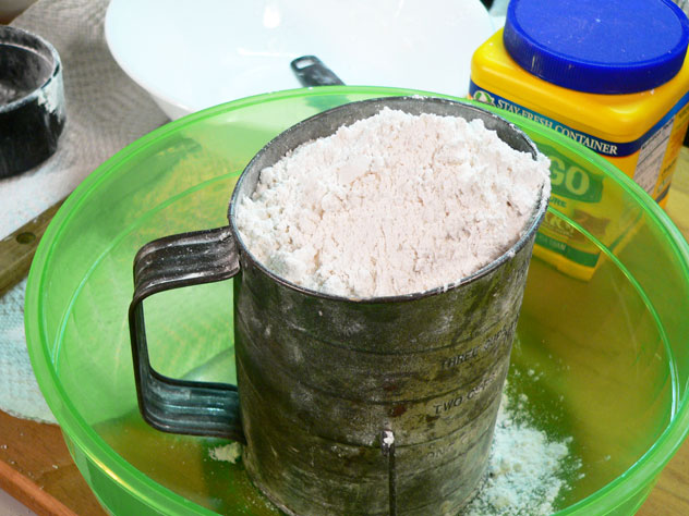 To make the Cake Flour, place the combined flour and corn starch in a sifter that you've placed in a mixing bowl. We'll need to sift the flour 3 different times, so you'll also need another mixing bowl.