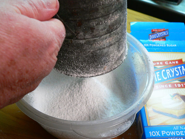 OK, this part got a bit messy. Spoon the Powdered Sugar into your sifter. Keep the sifter down in the bowl as much as possible as you sift the Powdered Sugar. I'm not sure why, but this produced a great deal of static, the more I turned the handle on the sifter. The sugar then decided it wanted to cling to my sifter, and to my body, flying in all directions out from under the sifter and attacking my kitchen.
