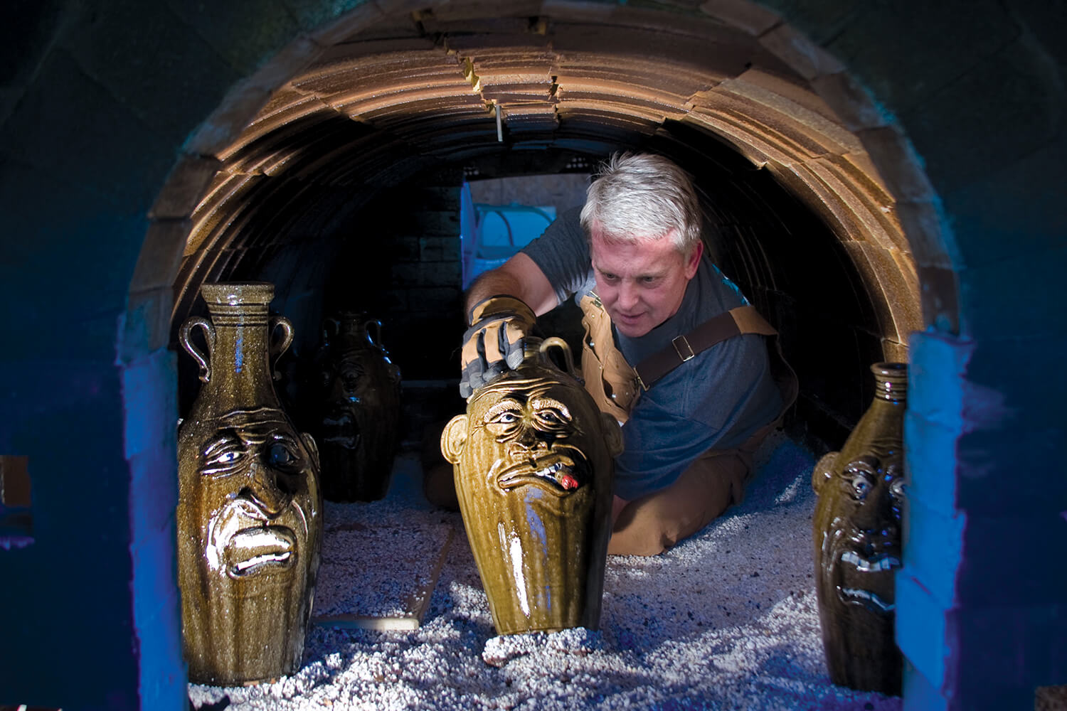 Potter Jeff Young retrieves finished pieces from his kiln in Vale, where he crafts jug faces.