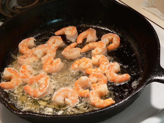 Stir and flip the shrimp for about two minutes, until they start showing good color. Then, remove them from the pan and let them cool. We'll chop them up once they cool down a bit. Resist the urge to eat them just like they are though, it'll be hard, but you can do it.