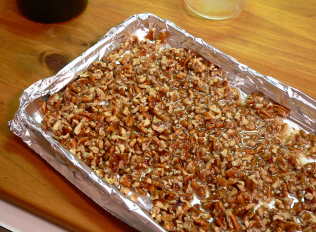 Realize that you don't have any parchment paper, and substitute by placing aluminum foil on a baking sheet. Parchment paper would be best if you have it on hand. Either way, spread the coated pecans out across the pan in a single layer.