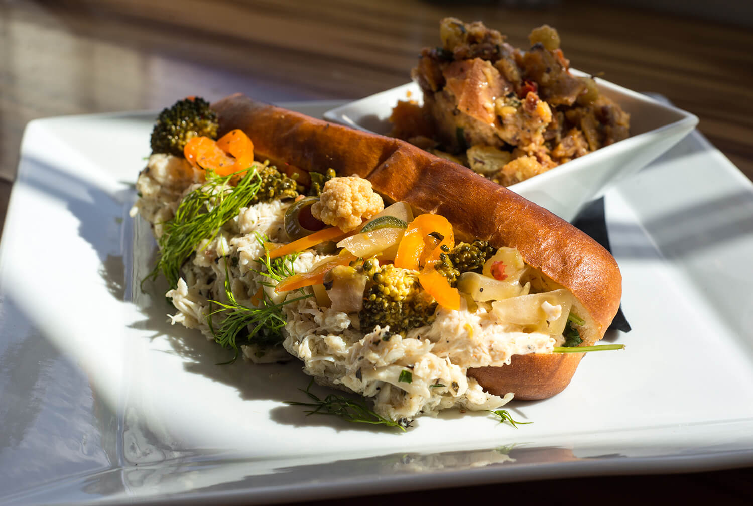 A buttery brioche roll is topped with lump crab, made bright by spiced lemon mayonnaise.