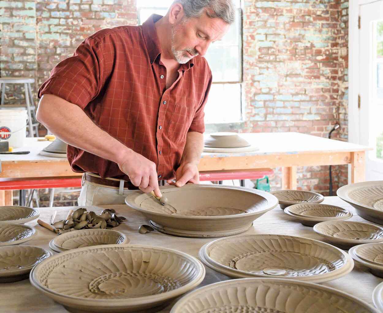 Image of North Carolina clay artist, Hamilton Williams, carving a platter from the new Nautilus Collection.
